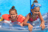 Kids on the mattress in the swimming pool — Stock Photo
