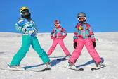 Three girls with ski on the snow — Stock Photo
