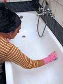 Woman cleaning bath — Stock Photo