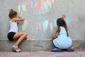 Children drawing on the wall with colored chalk — Stock Photo
