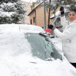 Woman cleaning snow from the car — Stock Photo