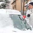 Woman cleaning snow from the car — Stock Photo #38137451