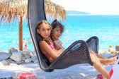 Children on the beach in swing — Stockfoto
