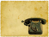 Old black phone on vintage background — Stock Photo