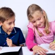 School children writing together - Stock Photo