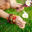 Hand with armlet picking wild flowers — Stock Photo #14132470