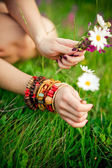 Hand with armlet picking wild flowers — Stock Photo