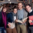 Group of happy students at a library — Stock Photo #14832969