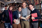 Group of happy students at a library — Stock Photo