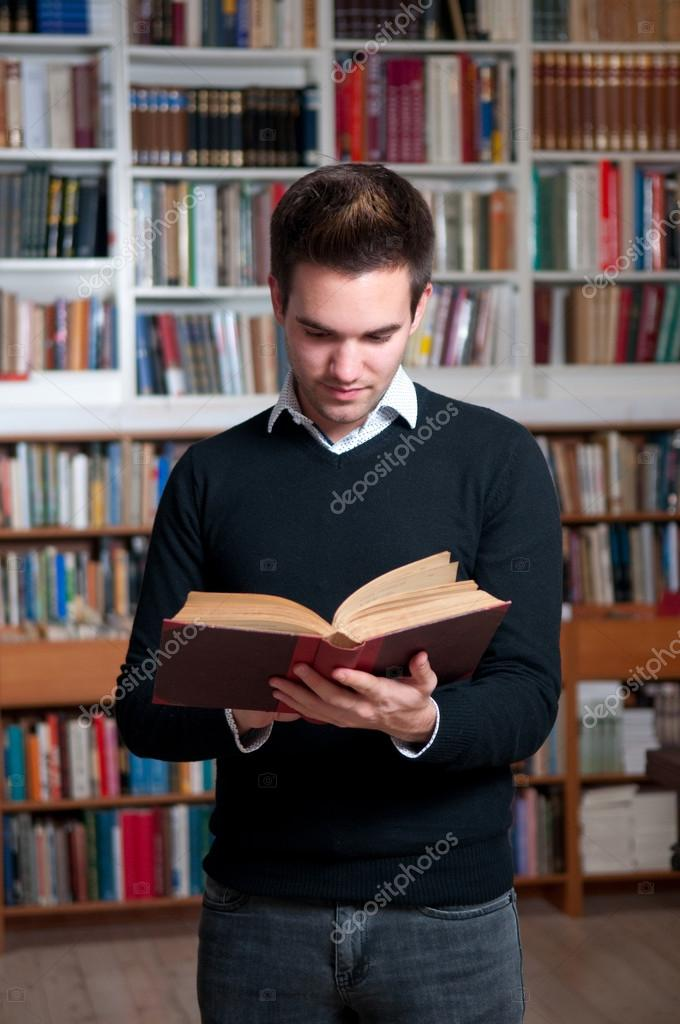 Male student standing in library, holding book. — Stock Photo #14853055