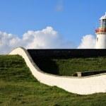 Irish Lighthouse on a green hill — Stock Photo