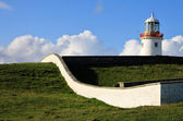 Irish Lighthouse on a green hill — Stock Photo