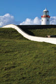 White Lighthouse on a green hill, Ireland — Stock Photo