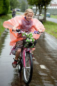 Girl cycling in the rain — Stock Photo