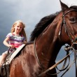 Blond girl on brown horse - Stock Photo