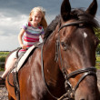 Young girl on big brown horse — Stock Photo
