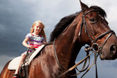 Blond girl on brown horse — Stock Photo