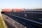 Red car leaves tunnel over highway in The Netherlands — Stock Photo