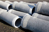Grey concrete pipes waiting — Stock Photo