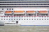 Small boat and large cruise ship — Stock Photo