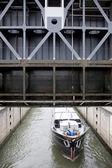 Ship leaving sluice under sluice door — Stock Photo