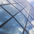Reflexions of clouds and blue sky in facade of modern building — Stock Photo #43062201