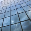 Reflexions of clouds and blue sky in facade of modern building — Stock Photo #43062417