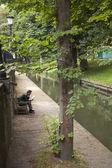 Man reading on bench at nieuwegracht in utrecht — Stock Photo