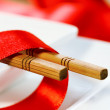 Chopsticks and red tape on a plate — Stock Photo