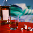 A bottle of alcohol, brandy glass and dice — Stock Photo