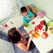 Stock Photo: Mother and child son cut vegetables for a meal food in the kitchen