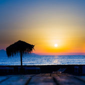 Palm beach umbrella on the beach during sunset — Stok fotoğraf