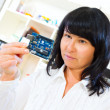 Stock Photo: Womworker checks printed circuit board microcontroller