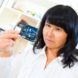 Woman worker checks the printed circuit board microcontroller — Stock Photo