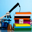 Microscope, books and chemical ware on a school table — Stock Photo #34954901