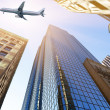 Plane flying over skyscrapers — Stock Photo