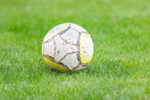 Old soccer ball on green grass — Stok fotoğraf
