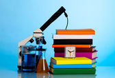 Microscope, books and chemical ware on a school table — Stock Photo