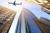 在摩天大楼上空飞行的飞机 — 图库照片