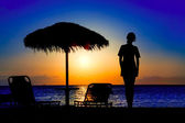 Silhouette of a girl on the beach during sunset — Stock Photo