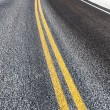 Yellow dividing line on asphalt road — Stock Photo #38078977