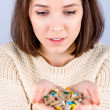 Stock Photo: Girl with pills in hand