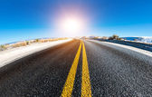Asphalt road and the sun in the sky — Stock Photo