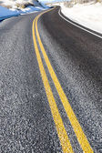 Yellow dividing line on asphalt road — Stock Photo