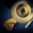 Cup of coffee and cookies on a black background — Stock Photo