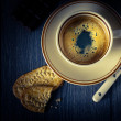 Stock Photo: Cup of coffee and cookies on a black background