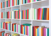 Books on a white shelf, stack of colorful books in Library — Stock Photo