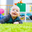Infant crawling on the green carpet in the child room — Stock Photo