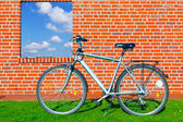 Bike at a brick wall with a window in the sky — Stock Photo