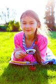 Girl looking through a magnifying glass on the grass — Stock Photo